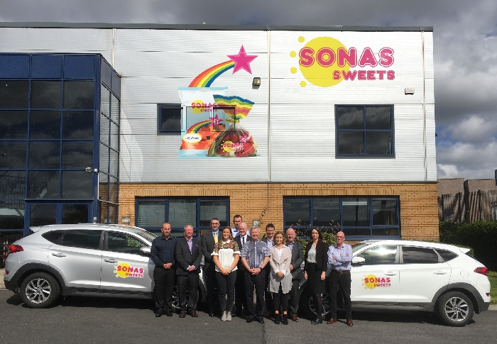 Group photo sonas banner and cars